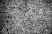 Abstract monochromatic B/W background in grunge style, obtained by shooting close up on stone wall surface and color treatment with Photoshop.
