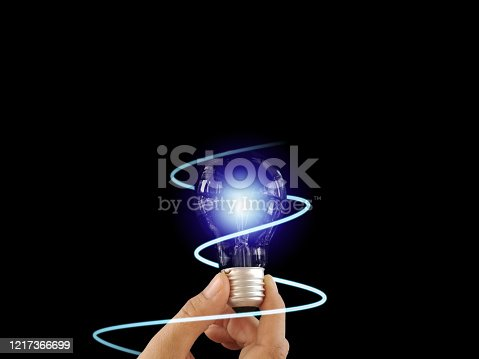 1007367156 istock photo Abstract hand holding creative light lightbulb on isolated black background. Present futuristic digital technology knowledge education. Concept of transformation innovation invention discovery 1217366699