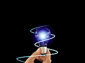istock Abstract hand holding creative light lightbulb on isolated black background. Present futuristic digital technology knowledge education. Concept of transformation innovation invention discovery 1217366699