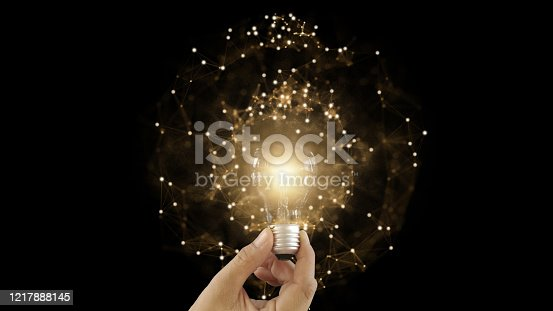 1007367156 istock photo Abstract hand holding creative light lightbulb on isolated black background. Present futuristic digital technology knowledge education. Concept of transformation innovation invention discovery 1217888145