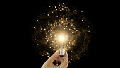 istock Abstract hand holding creative light lightbulb on isolated black background. Present futuristic digital technology knowledge education. Concept of transformation innovation invention discovery 1217888145