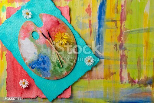 Abstract hand painted in vivid colors on watercolor turquoise and red papers with painter artist palette and brushes and spring daisy flowers
