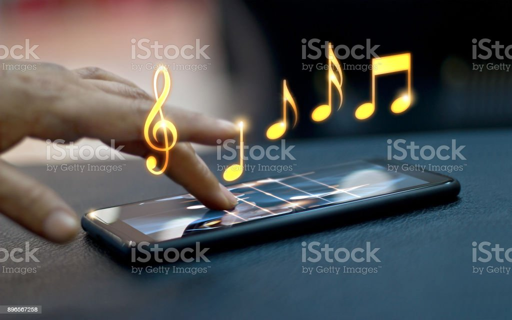 Abstract hand playing music notes on smartphone at night background, music concept, All on mobile screen are design up. stock photo