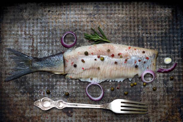 abstrakte hering fisch mit gewürzen auf alte grunge metallplatte kreative stillleben - silberzwiebeln stock-fotos und bilder