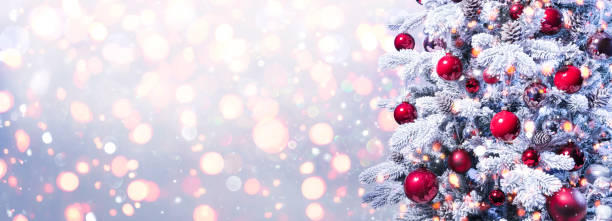 Abstract Holiday Background - Snowy Christmas Tree With Red Baubles With Shiny Defocused Lights stock photo