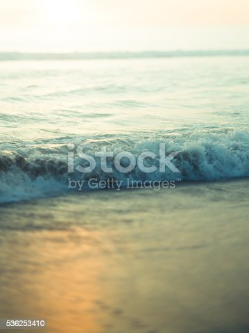 Abstract toned photo of ocean and sand at sunset. Actual tilt/shift lens used to exaggerate blur.