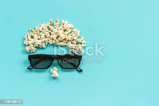 956942702 istock photo Abstract image of viewer, 3D glasses and popcorn on blue background. Concept cinema movie and entertainment Flat lay Top view Copy space Template for text or your design 1156188722