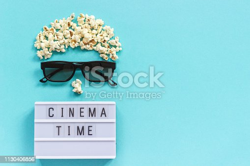 istock Abstract image of viewer, 3D glasses, popcorn and light box text Cinema time on blue paper background. Concept cinema movie and entertainment Flat lay Top view Copy space for text or your design 1130406856