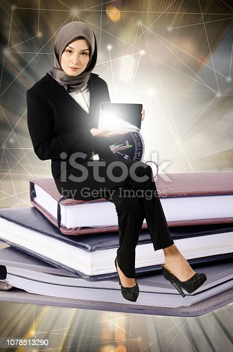 istock Abstract image of young businesswoman with tablet sitting on book stack over abstract double exposure background 1078513290