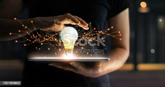 Abstract. Innovation. Hands holding tablet with light bulb future technologies and network connection on virtual interface background, innovative technology in science and communication concept.