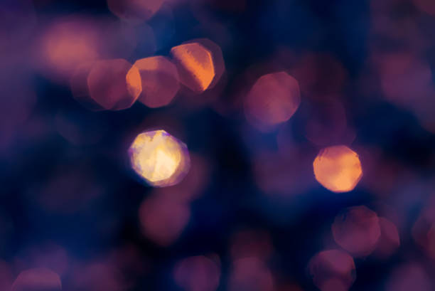 Abstract lens bokeh purple gold background Out of focus rings result in these purple and gold out-of-focus discs, a soft lens bokeh. A pleasant dark abstract background. whiteway stock pictures, royalty-free photos & images