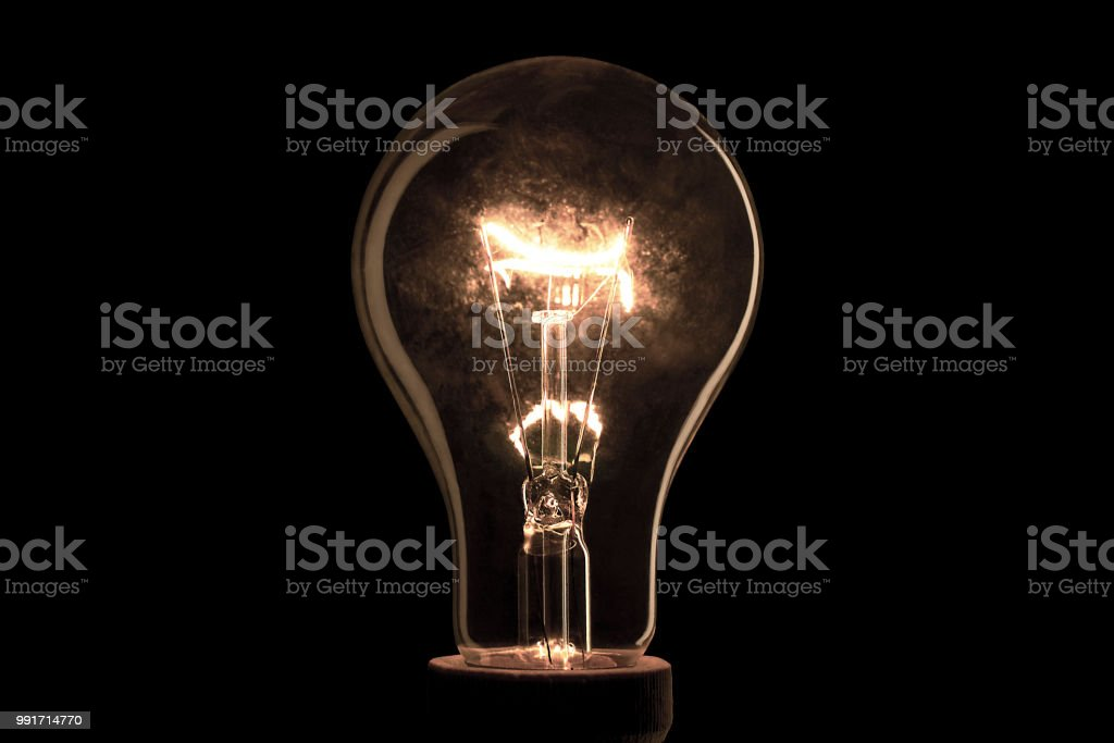 Realistic light bulb on the black background. Lamp light in the dark....