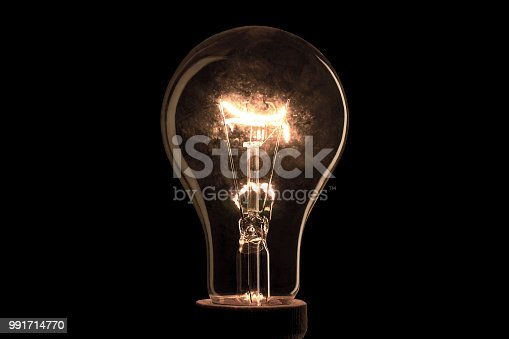 istock Abstract light bulb on the black background. Lamp light in the dark. Electric bulb. Glowing light in the dark. 991714770
