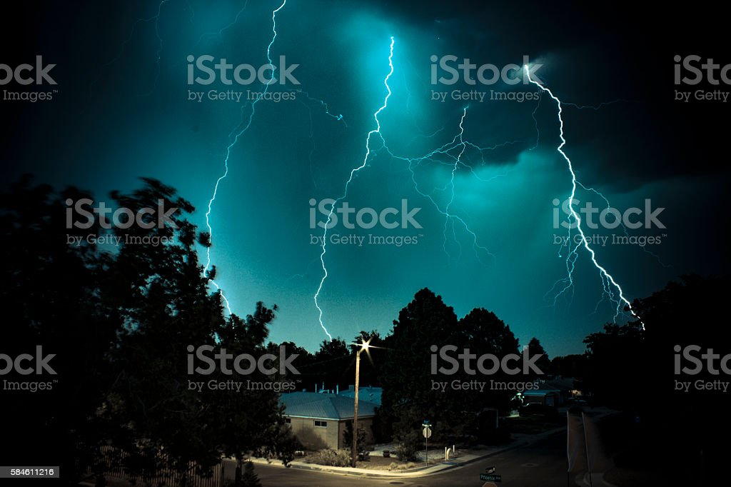 Abstract lightning horror with lit house in foreground stock photo