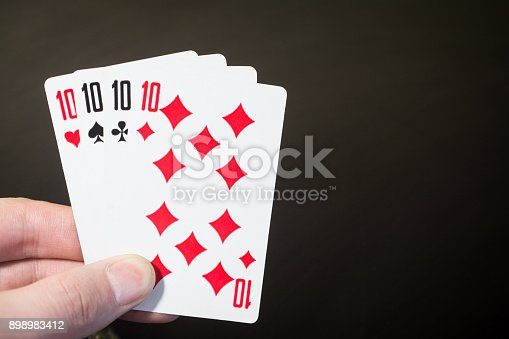 istock Abstract: man hand holding playing card four Ten isolated on black background with copyspace 898983412