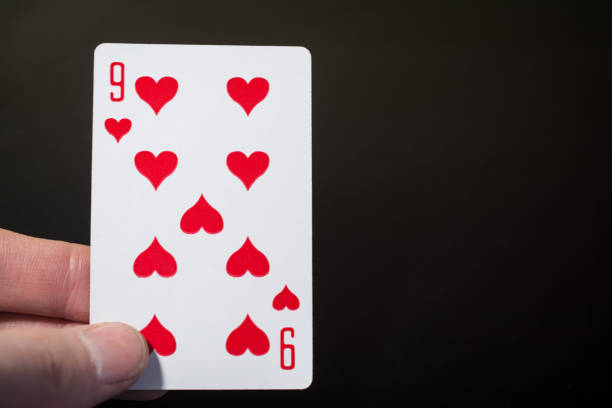 Abstract: man hand holding playing card nine of hearts on a black background with copyspace stock photo