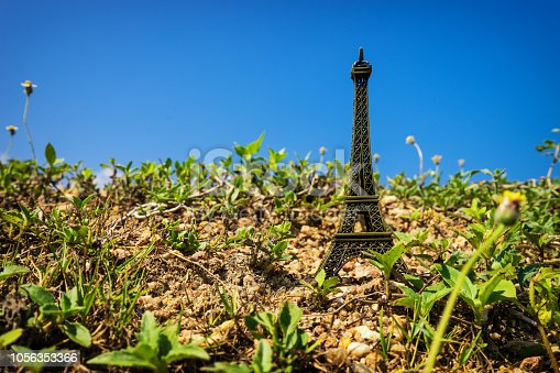 istock abstract mini Eiffel Tower on ground and blue sky - can use to display or montage on product 1056353366