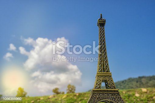 istock abstract mini Eiffel Tower with sun light on ground and blue sky - can use to display or montage on product 1056355960