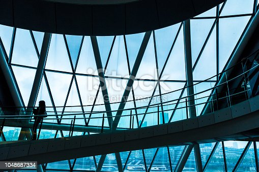 Wide angle color image depicting ultra modern contemporary interior architecture in City Hall (a public building in London that is open to the public) in London, UK. The silhouette of a lone woman is visible as she walks down the modern spiral staircase. In the background we can see some of the skyscrapers that dominate the skyline of London. Lots of room for copy space.