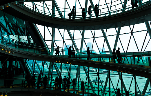 Wide angle color image depicting ultra modern contemporary interior architecture in City Hall (a public building in London that is open to the public) in London, UK. Crowds of people in silhouette and unrecognizable are walking down the modern spiral staircase. In the background we can see some of the skyscrapers that dominate the skyline of London. Lots of room for copy space.