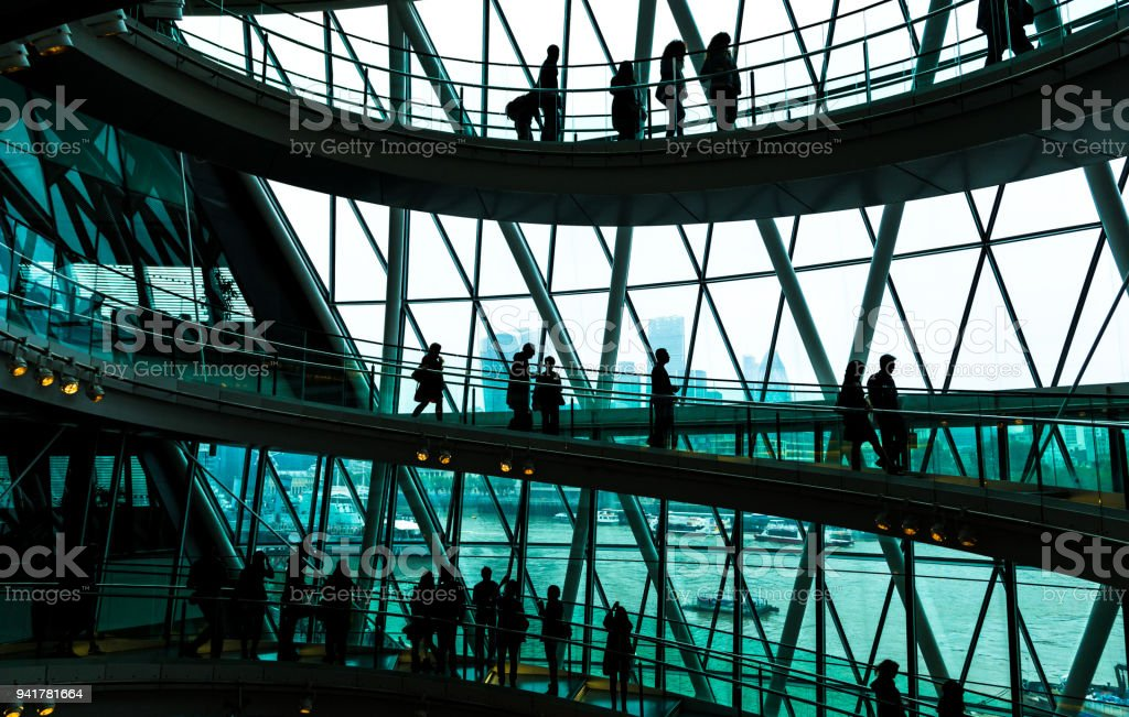 Abstract modern architecture and silhouettes of people on spiral staircase stock photo