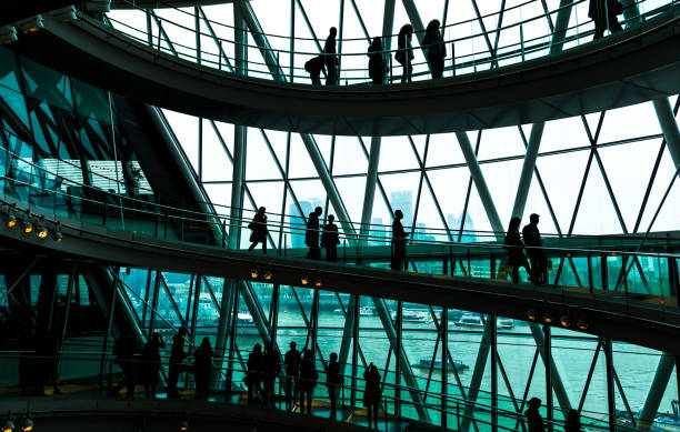 abstract modern architecture and silhouettes of people on spiral staircase - uk travel stock photos and pictures