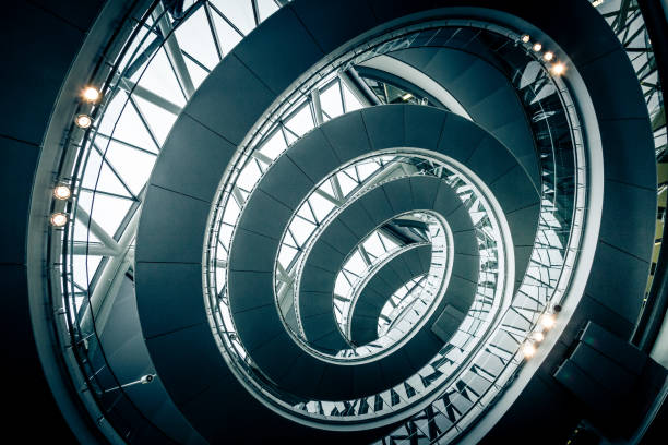 Abstract modern architecture and winding staircase in the city Wide angle color image depicting ultra modern contemporary interior architecture in City Hall (a public building in London that is open to the public) in London, UK. Looking up we can see a modern spiral staircase winding around the entire building, and also the windows that surround the building, letting in as much natural light as possible. Lots of room for copy space. ***IMAGE SHOT IN CITY HALL, LONDON, UK, A PUBLICLY OWNED BUILDING FREELY ACCESSIBLE TO THE PUBLIC. PLEASE NOTE THERE NO FEES OR TICKETS ARE REQUIRED TO ENTER, AND THERE ARE NO PHOTOGRAPHIC RESTRICTIONS*** architectural feature stock pictures, royalty-free photos & images