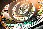 Color image depicting ultra modern contemporary interior architecture in City Hall (a public building in London that is open to the public) in London, UK. Looking up we can see a modern spiral staircase winding around the entire building, and also the windows that surround the building, letting in as much natural light as possible. Lots of room for copy space.
