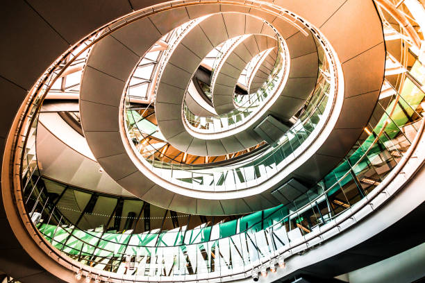 Abstract modern architecture and winding staircase in the city Color image depicting ultra modern contemporary interior architecture in City Hall (a public building in London that is open to the public) in London, UK. Looking up we can see a modern spiral staircase winding around the entire building, and also the windows that surround the building, letting in as much natural light as possible. Lots of room for copy space. central london stock pictures, royalty-free photos & images