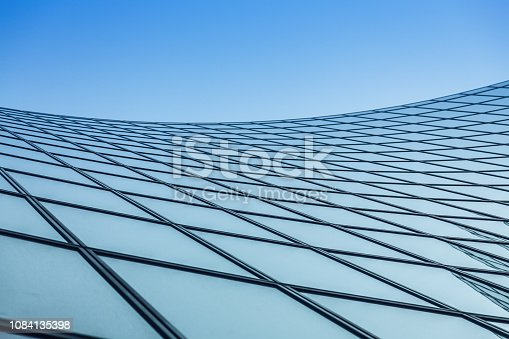 Abstract waving metal and glass architectural pattern on blue sky