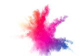 白い背景の上の抽象的な多色粉塵爆発。 カラースプ ラッシュ塵粒子の動きを凍結します。塗装のホーリー