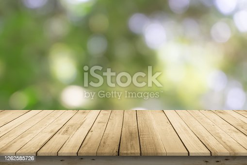 Abstract natural spring blurred garden leaves view from living room window with wooden table counter background for show, promote, Create light soft colors design banner ads on display concept.