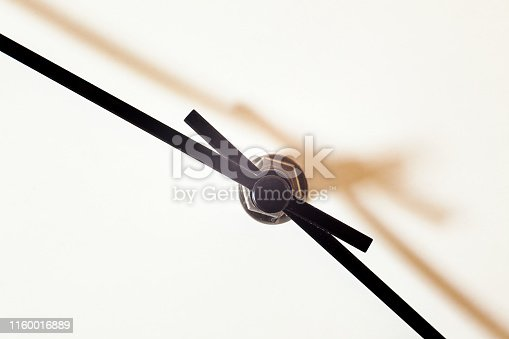 Closeup view of a simple wall watch, details of minute and hour hands on white background.