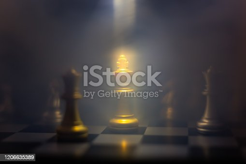 istock Abstract of business concept. Golden king is the most important on chessboard. King stand in dark with streamer. Company has to have intelligent of leadership for bringing the company to the goals. 1206635389
