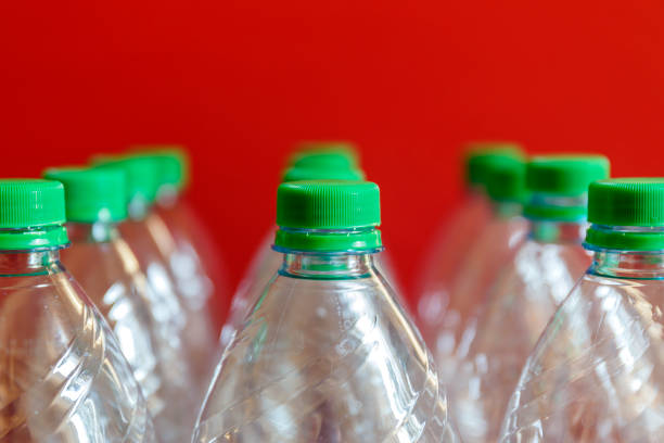abstract of group of water plastic bottles with green bottle caps on red background - plastic cap stock pictures, royalty-free photos & images