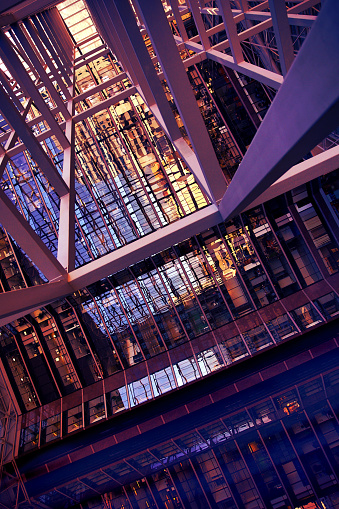 This is a colorful abstract photo of an office building with large glass windows.