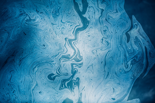 Blue oil slick on water surface. Water pollution