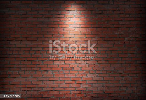 istock abstract old brick wall in the dark with spotlight warm light tone. 1027892522