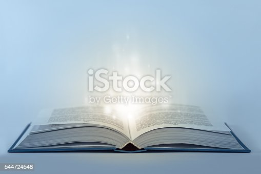 istock Abstract open magic book on table with light inside 544724548