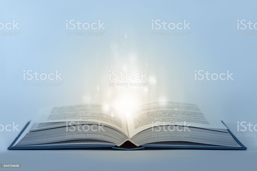 Abstract open magic book on table with light inside stock photo