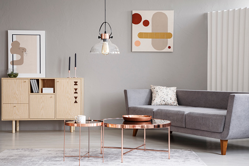 Abstract paintings on a gray wall of a classy living room interior with a wooden sideboard and shiny golden coffee tables