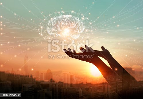 istock Abstract palm hands touching virtual brain with network connections, innovative technology in science and communication concept 1069554568