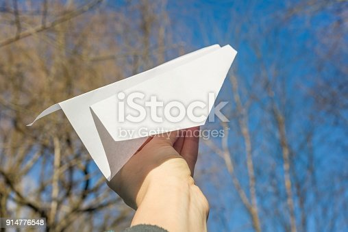 658921430 istock photo Abstract paper plane in hand, blue sky, spring trees sun background 914776548
