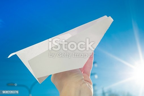 istock Abstract paper plane, in hand, sky, sun background 908205076