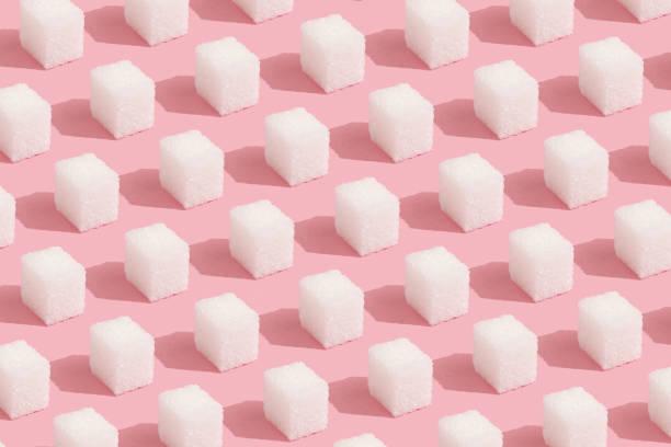 abstract muster aus zuckerwürfeln auf rosa minimal-stil hintergrund - würfelzucker stock-fotos und bilder