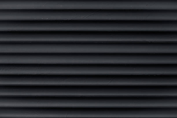 abstract pattern of lines. texture of black corrugated metallic surface. dark ribbed background with stripes, straight lines. modern pattern of gray metal jalousie. closed metallic jalousie. - żebrowany zdjęcia i obrazy z banku zdjęć
