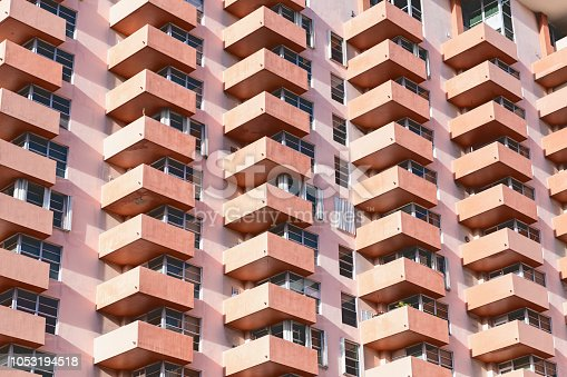 istock Abstract pattern view on residential, apartment complex building with many windows, balconies painted in pink, orange during sunny day 1053194518