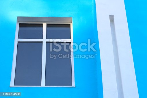 abstract photo of a darkened window with a partition cross on a blue wall and a white rectangular column
