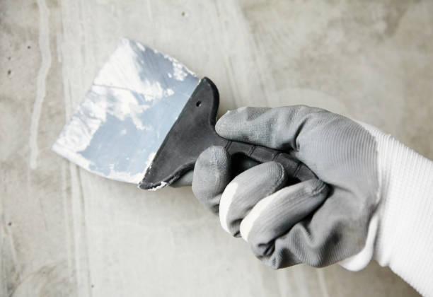 abstracte foto van de muur afwerking werk, troffel in de handen van een werknemer op een bouwplaats, decoratieve reparatie - foto's van hands stockfoto's en -beelden