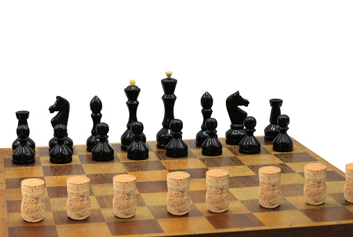 Abstract photo with chess pieces and wine corks on chessboard isolated on white background